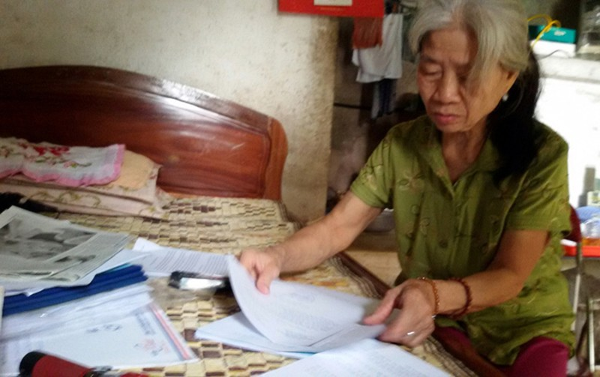 Người phụ nữ 72 tuổi vẫn xếp hàng chồng đơn ngày ngày gõ cửa các cơ quan để mong vụ việc được giải quyết dứt điểm. Ảnh: Tràng An