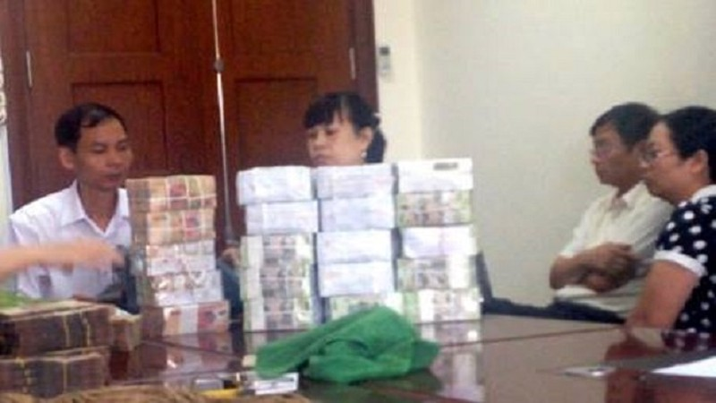 Ông Đinh Ngọc Uyên, Phó Giám đốc Côgn ty TNHH MTV Cảng Quảng Ninh (áo trắng ngồi đầu bên phải) giao nộp tiền cho cơ quan chức năng
