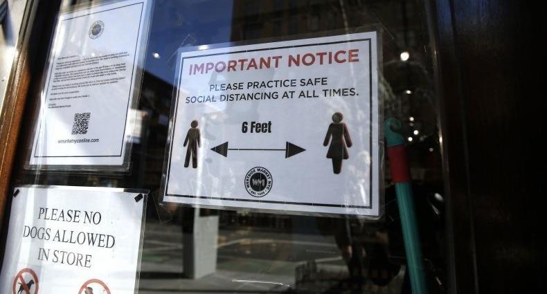 """Một thông báo giữ """"khoảng cách xã hội"""" trên một cửa hàng tạp hóa khi Thành phố New York nỗ lực làm giảm sự lây lan của Covid-19. Ảnh: Getty Images"""