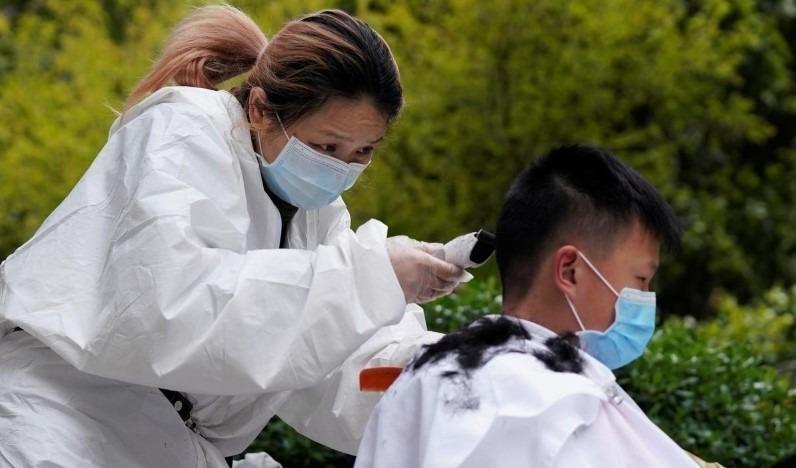Thợ cắt tóc Quân Phương, 39 tuổi, cắt tóc của khách hàng tại một khu dân cư ở Vũ Hán, Hồ Bắc, Trung Quốc (COVID-19), ngày 30/3/2020. Ảnh: Reuters.