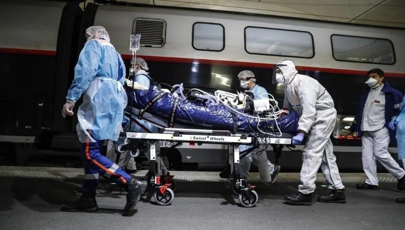 Nhân viên y tế chuyển một bệnh nhân bị nhiễm Covid-19 sang một chuyến tàu tại nhà ga Voyusterlitz ở Paris. Ảnh: AP