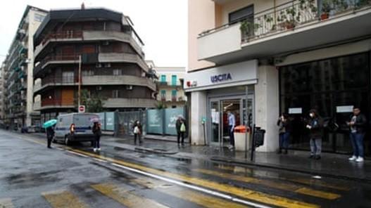 Người mua sắm xếp hàng trong mưa ở Sicily, Ý. Ảnh: Reuters