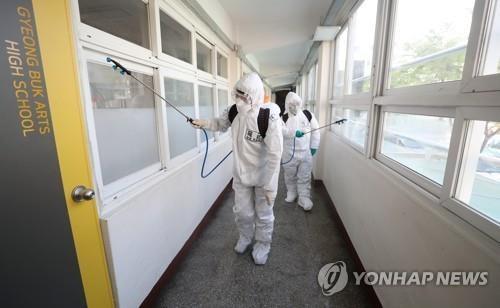 Quân y đang khử trùng một hành lang bên trong trường trung học nghệ thuật Gyeong Buk ở Daegu , ngày 14/4/2020.