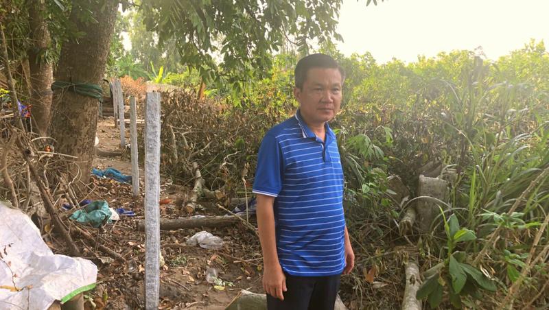Ông Nguyễn Thành Nam buồn bã vì không thể hoàn thiện việc xây dựng hàng rào để bảo vệ vườn mít của mình.