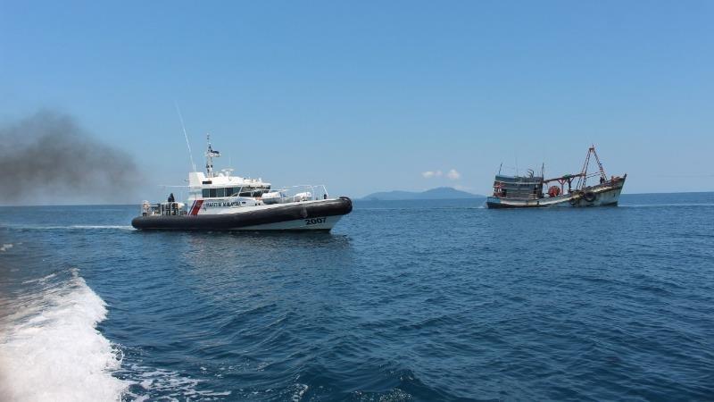 Tàu tuần tra của Malaysia áp tải tàu cá Việt Nam (phải) vào bờ - Ảnh: MMEA/Tuổi trẻ