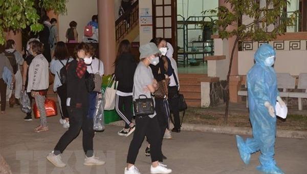 Nhân viên y tế hướng dẫn công dân trở về vào khu vực cách ly tại Tiền Giang. (Ảnh: Nam Thái/TTXVN)