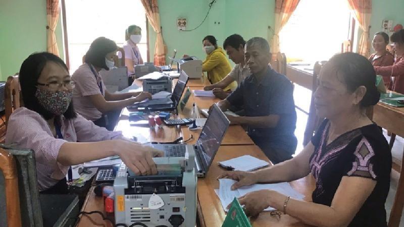 Chị Nguyễn Thị Nga (phải), Tổ trưởng Tổ TK&VV bản Cây Sú, đang giao dịch với NHCSXH huyện tại Điểm giao dịch xã Trường Sơn.