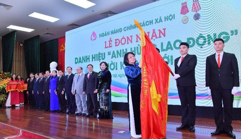 """Phó Chủ tịch nước Đặng Thị Ngọc Thịnh đính huy hiệu """"Anh hùng lao động"""" thời kỳ đổi mới lên lá cờ truyền thống của NHCSXH."""
