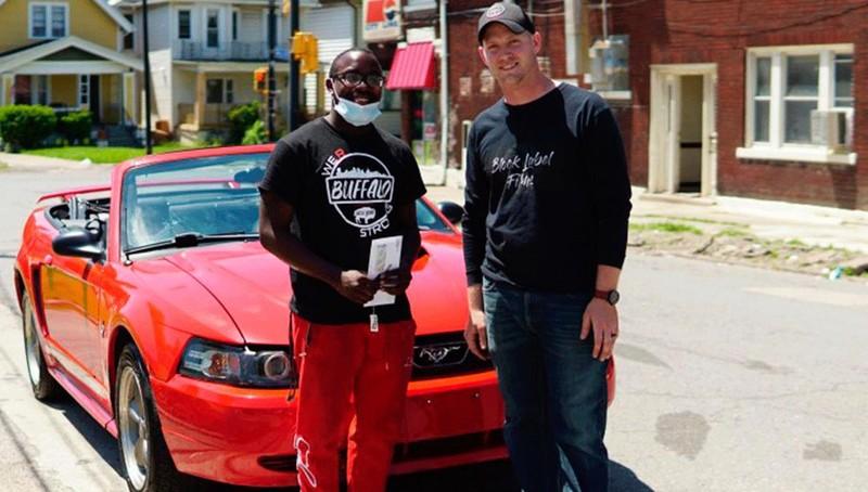Antonio Gwynn Jr. (trái) được Matt Block tặng chiếc xe mui trần màu đỏ khi một mình dọn dẹp rác thải sau cuộc biểu tình. Ảnh: Matt Block