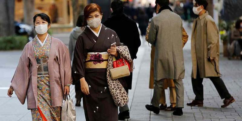 Hai người phụ nữ mặc kimono và đeo khẩu trang đi bộ ở Tokyo, Nhật Bản vào ngày 13/11. Ảnh: REUTERS.