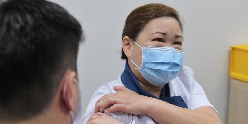 Y tá Sarah Lim được tiêm vắc-xin tại Trung tâm Quốc gia về Các bệnh Truyền nhiễm. Ảnh: AFP.