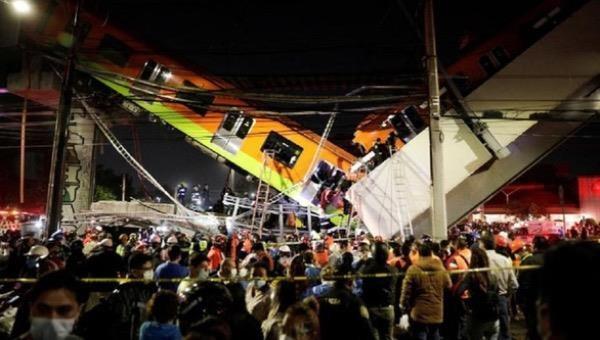 Nhân viên cứu hộ bắc thang lên toa tàu để giải cứu những hành khách bị mắc kẹt sau tai nạn sập cầu vượt metro ở thủ đô Mexico City, ngày 3/5.