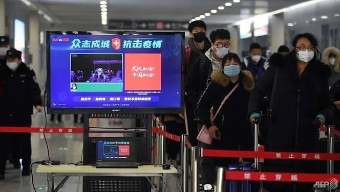 Hành khách đi qua máy kiểm tra thân nhiệt tại Trung Quốc.