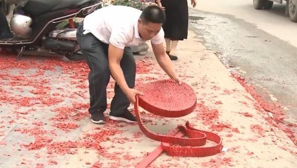 Người đàn ông rải cuộn pháo ra vỉa hè, trước ngôi nhà tổ chức đám cưới. Ảnh: Facebook.