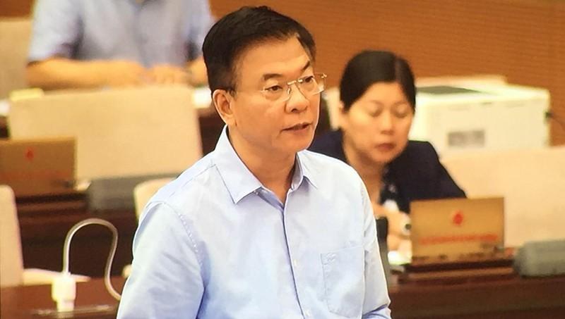 Bộ trưởng Bộ tư pháp trình bày báo cáo của Chính phủ tại phiên họp.