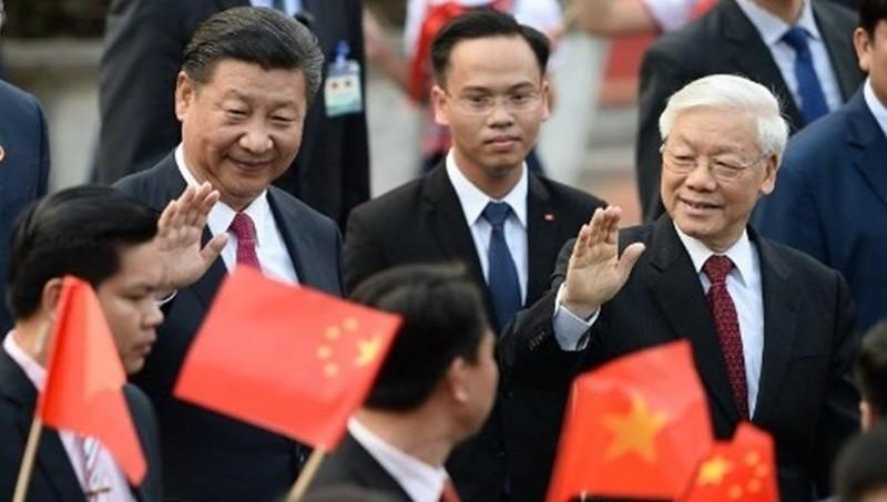Tổng Bí thư Nguyễn Phú Trọng và Chủ tịch Trung Quốc Tập Cận Bình chào học sinh cầm quốc kỳ Việt Nam và Trung Quốc trong lễ đón tại Phủ Chủ tịch, Hà Nội ngày 12/11/2017.