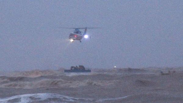 Trực thăng tiếp cận tàu chìm để thả dây và đường, sữa cho 9 người mắc kẹt.