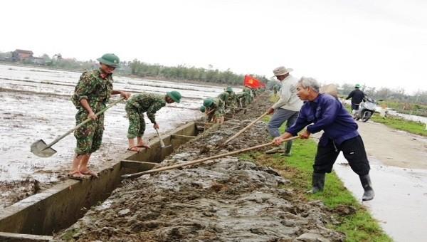 Cán bộ, chiến sĩ giúp nhân dân vét bùn tại các kênh mương nội đồng