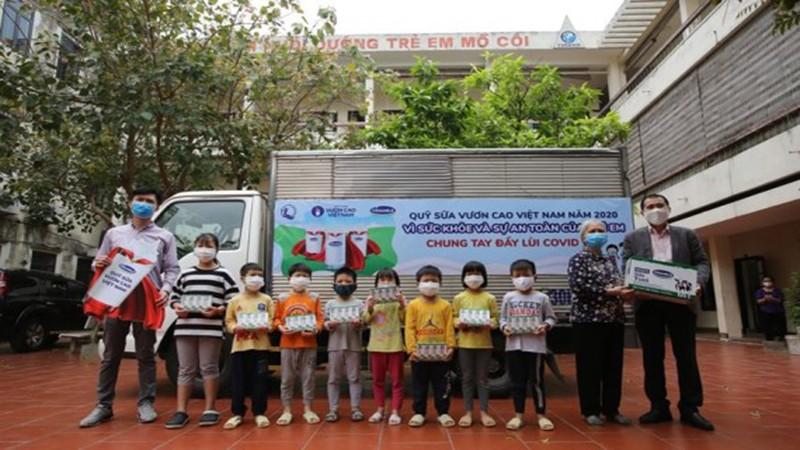 Đại diện Công ty Vinamilk tặng sữa cho trẻ em.