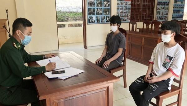 Lực lượng chức năng đang làm việc với hai thanh niên vượt biên trái phép từ Lào về Việt Nam.