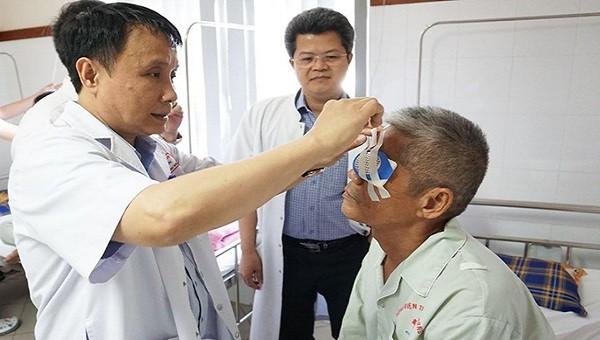 GS. TS Phạm Như Hiệp, Giám đốc Bệnh viện Trung ương Huế tháo băng cho bệnh nhân Phan Hữu Lạc sau ca ghép giác mạc