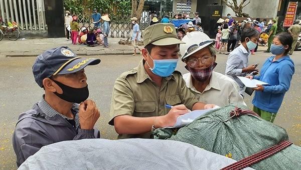 Người dân nhờ cán bộ dân phố điền thông tin vào phiếu hẹn phát gạo.