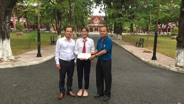 Nhà báo Nguyễn Quang Tám - Trưởng Văn phòng Đại diện Báo PLVN khu vực Bình Trị Thiên (trái) trao số tiền bạn đọc  ủng hộ em Nhung.