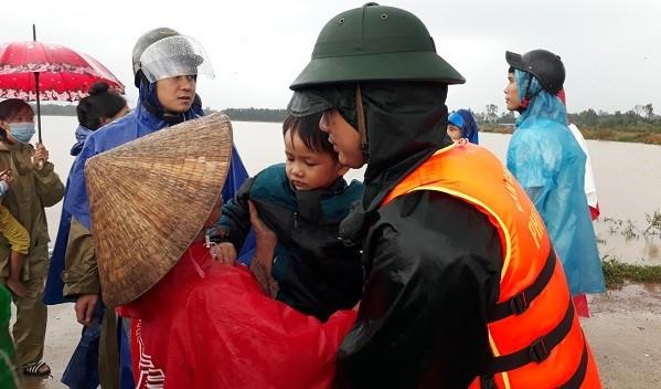 Cán bộ, chiến sĩ Ban CHQS huyện Phú Lộc, Bộ CHQS tỉnh Thừa Thiên Huế di dời người dân thôn Châu Thành đến nơi tránh trú an toàn.