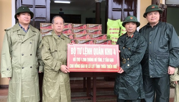 Trung tướng Nguyễn Doãn Anh, Tư lệnh Quân khu 4 (thứ 2 bên phải) trao hỗ trợ cho đại diện lãnh đạo tỉnh - ông Phan Ngọc Thọ.