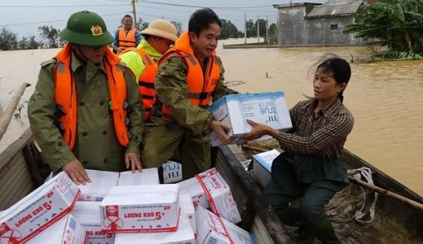 Đại tá Nguyễn Tiến Nam, Giám đốc Công an tỉnh trao nhu yếu phẩm cho bà con vùng lũ.