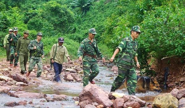 Các cán bộ chiến sĩ Đồn Biên phòng Cà Ròong phối hợp với dân quân địa phương tuần tra tuyến biên giới.
