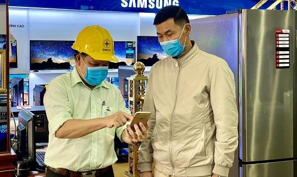 Nhân viên Điện lực Quảng Bình hướng dẫn khách hàng thanh toán tiền điện qua các ứng dụng trên điện thoại thông minh.