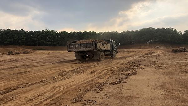 Các xe chở đất đầy đất nhưng chỉ được che chắn tạm bợ.