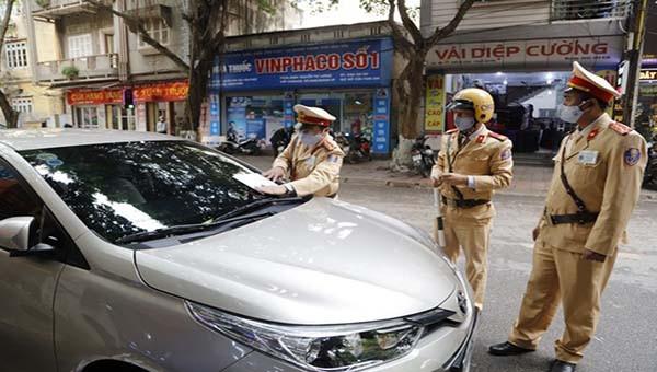 Lực lượng CSGT Công an tỉnh Vĩnh Phúc tiến hành xử phạt nguội và dán giấy thông báo xe ô tô dừng, đỗ sai quy định.