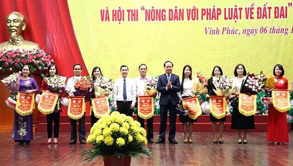 Chủ tịch Hội Nông dân tỉnh Nguyễn Thanh Tùng và Giám đốc Sở Tư pháp Nguyễn Văn Bắc tặng hoa và cờ lưu niệm cho các đội tham dự hội thi