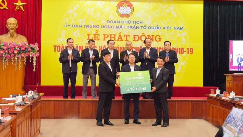 Đ/c Nghiêm Xuân Thành – Chủ tịch HĐQT Vietcombank (đứng giữa) - trao biển tượng trưng số tiền ủng hộ công tác phòng, chống dịch Covid-19 của Vietcombank.
