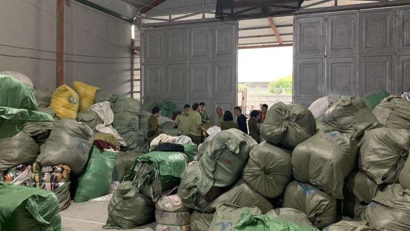 """Lực lượng chức năng kiểm tra kho quần áo """"sida"""" ở thôn Đông Thành."""