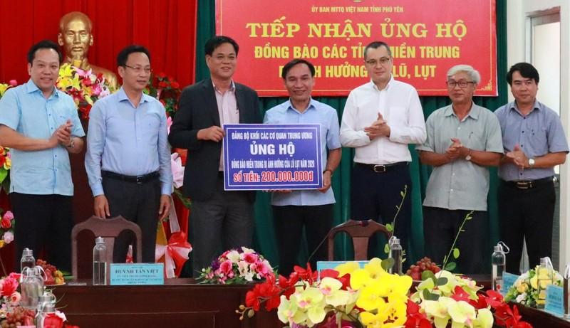 Bí thư Đảng ủy Khối các cơ quan Trung ương Huỳnh Tấn Việt (thứ 3 từ trái sang) trao bảng biểu trưng ủng hộ 200 triệu đồng cho tỉnh Phú Yên. Ảnh: Lê Dũng.