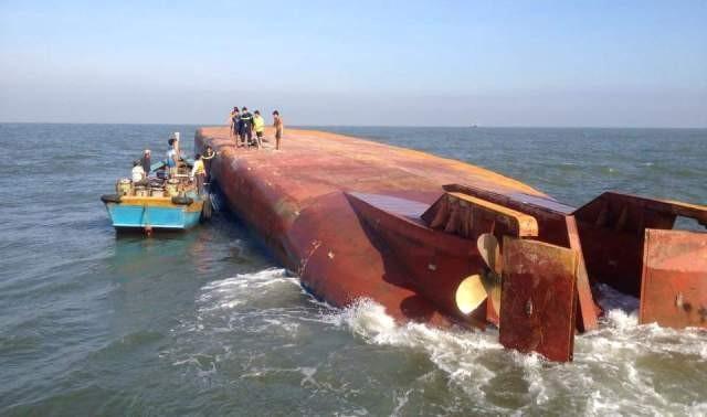 Con tàu lật úp, để lộ nguyên phần đáy lên trên mặt nước, ảnh báo Lao động