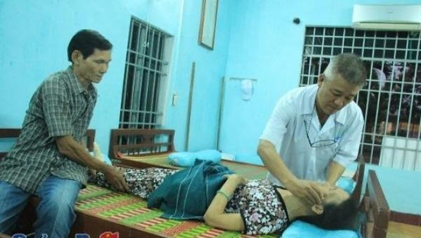 Lương y Nguyễn Khắc Dưỡng (bìa phải) khám bệnh miễn phí cho người nghèo