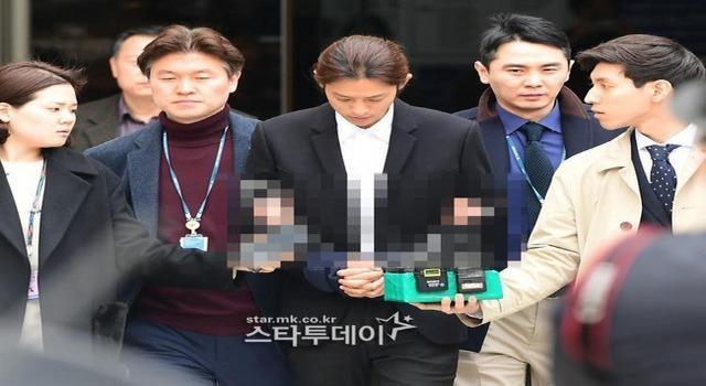 Hình ảnh Jung Joon Young cúi đầu khi bị áp giải.