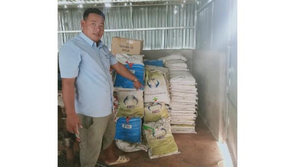 Ông Nguyễn Trọng Hữu bên đống hàng thức ăn tôm tồn kho nhưng không được Cty NewHope thanh toán.