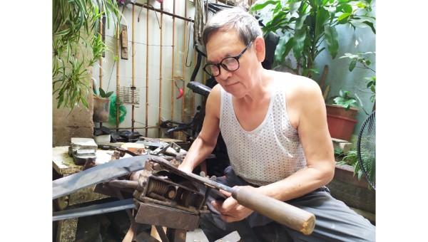 Nghệ nhân Phạm Quang Xuân với công đoạn xẻ quai dép.