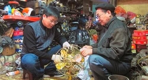Ông Phúc (phải) và anh Đức đang phục chế một cây quạt cổ. Ảnh tư liệu.
