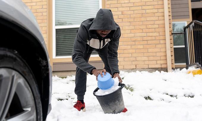 Không có nước uống, người dân phải múc băng tuyết để đun lấy nước sử dụng.