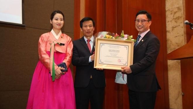 Ông Lý Xương Căn (bìa phải) nhận quyết định làm Đại sứ du lịch Việt Nam từ Bộ trưởng Bộ VH,TT&DL Nguyễn NgọcThiện.