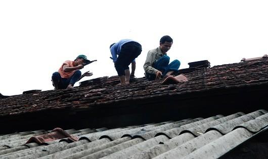 Những hộ gia đình bị thiệt hại, được chính quyền và bà con giúp đỡ lợp lại mái ngói
