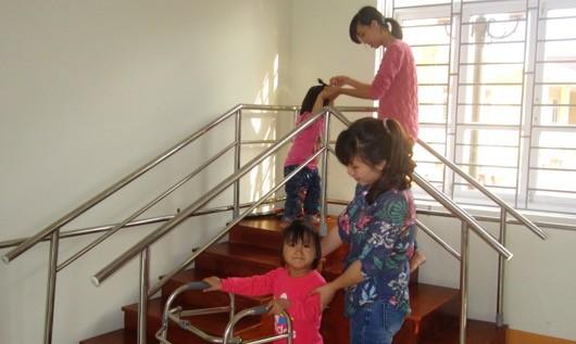 : Nhân viên Trung tâm đang hướng dẫn các em bài tập phục hồi chức năng