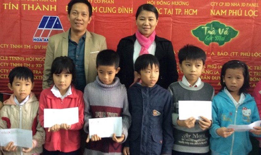 Ông Mai Quốc Bảo, Đại diện Công ty Trà Vả Lộc Mai tặng quà cho các em học sinh.