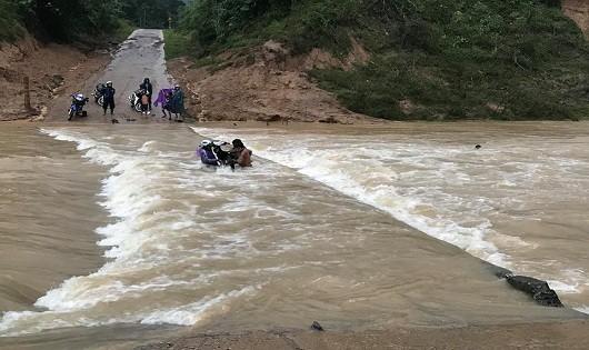 Mặc dù tại cầu tràn nước chảy xiết nhưng 4 thanh niên vẫn liều mình đưa xe máy vượt qua (ảnh Đoàn Nhật Thái)